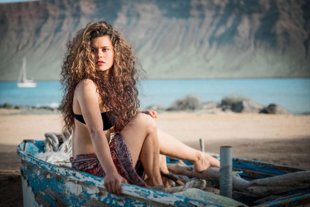 Wild girl on a beach in a boat